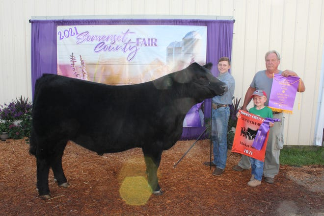Braden Durst, 14, of Berlin, sold his Grand Champion Steer for $5.50 a pound to Andy and Brenda Ansell, with Andy and Josiah, 6, holding the banners during the livestock sale at the Somerset County Fair on Saturday. Check out the Daily American's website at www.dailyamerican.com for photo galleries, video and stories from the 2021 Somerset County Fair.
