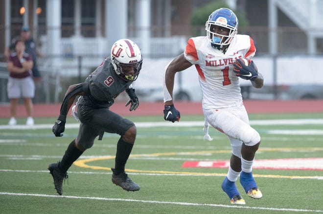 Millville's LeQuint Allen runs the ball past Union's Omar Ibrahim during the Battle at the Beach football game played in Ocean City on Saturday, August 28, 2021.  Millville defeated Union, 31-28.