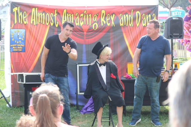 C.J. Campbell, 12, center, performs some magic tricks with the help of Almost Amazing Rex and Dana at the Sandusky County Fair on Saturday.