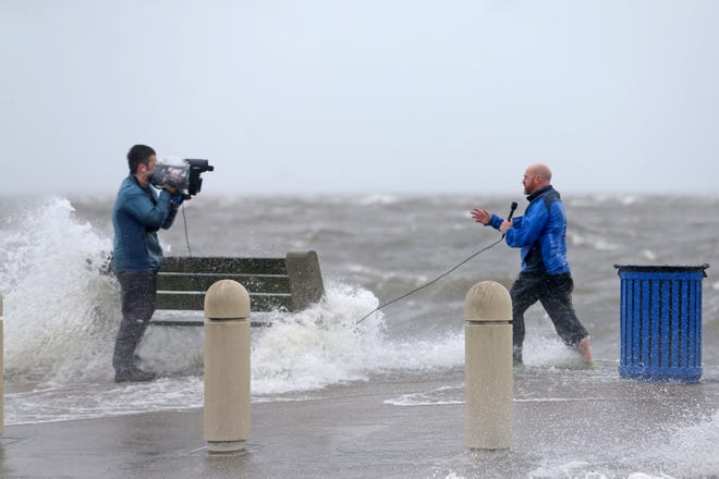 A news crew films as storm surge pushes water from Lake Pontchartrain over Lakeshore Drive as the effects of Hurricane Ida begin to be felt in New Orleans on Sunday, Aug. 29, 2021.