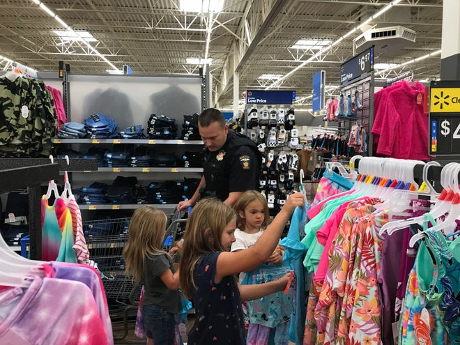 Mansfield police Officer Mark Boggs hands out police badge stickers to kids during Cops N Kids Sunday at Walmart on Possum Run Road during the 25th annual shopping event.