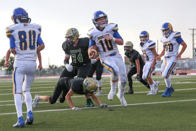 Bloomfield quarterback Ryan Sharpe (10) gets past Hope Christian defenders Logan Saul (23) and Zach Lapierre (74) for a touchdown in the third quarter of their game, Saturday, August 29 at Milne Stadium in Albuquerque