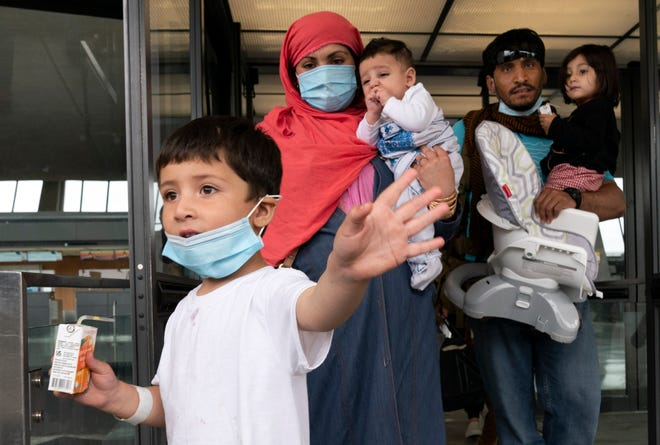 Families evacuated from Kabul, Afghanistan, walk through the terminal before boarding a bus after they arrived at Washington Dulles International Airport, in Chantilly, Va., on Sunday, Aug. 29, 2021. (AP Photo/Jose Luis Magana)