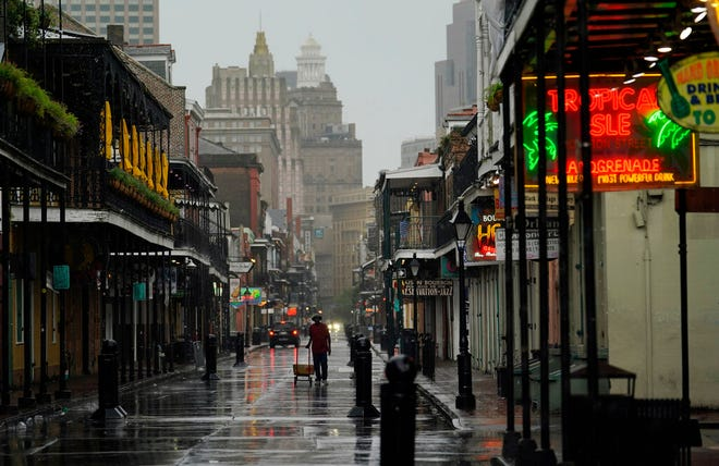 A man pulls a cart down a mostly deserted Bourbon Street in the French Quarter as the early effects of Hurricane Ida are felt, Sunday, Aug. 29, 2021, in New Orleans, La. (AP Photo/Eric Gay)