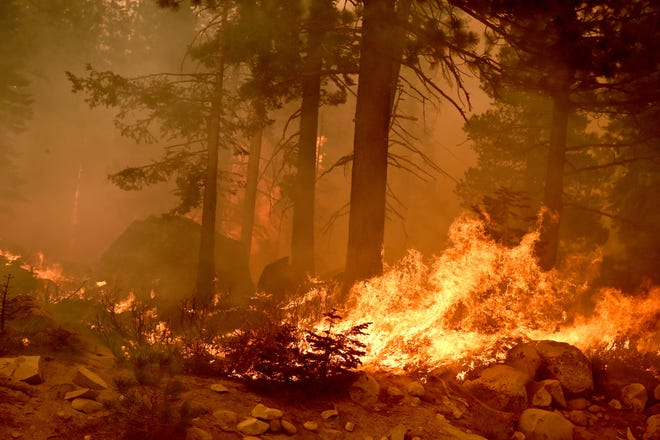 The Caldor Fire burns on both sides of the U.S. 50 11 miles from the Meyers neighborhood in South Lake Tahoe, Calif., on Aug. 29, 2021.