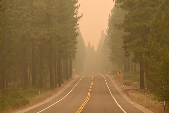 A lone car moves through the thick smoke along the US-50 near the Meyers neighborhood in South Lake Tahoe on Sunday.