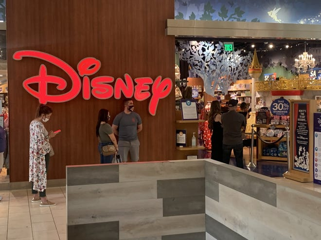 Shoppers wait outside the Disney Store at the Oaks mall in Thousand Oaks Saturday. The site is among nearly 60 closing nationwide by Sept. 15, 2021.