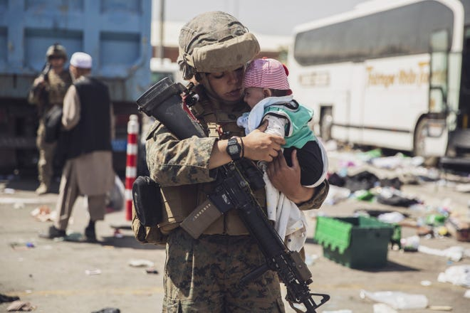 A Marine with the 24th Marine Expeditionary Unit carries a baby at Hamid Karzai International Airport in Kabul, Afghanistan, on Aug. 28, 2021.
