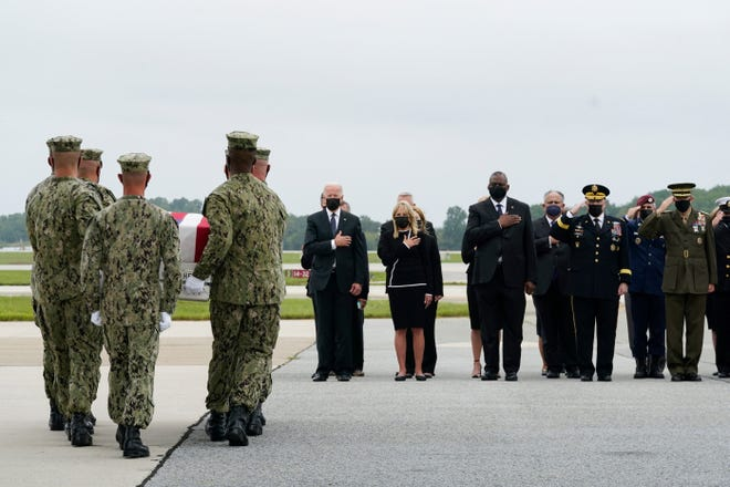 President Joe Biden watches as a Navy carry team moves a transfer case containing the remains of Navy Corpsman Maxton W. Soviak, 22, of Berlin Heights, Ohio, on Aug. 29 at Dover Air Force Base in Delaware.