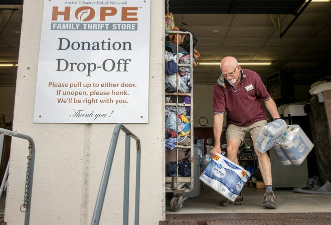 Lee Adams of Austin Disaster Relief Network's HOPE Family Thrift Store accepts donated toilet paper for people affected by Hurricane Ida on Monday.