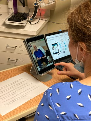 Dr. Julie Kurek, a neurologist at AU Health System, is connected remotely with patient Richard Martinez, 79, in Griffin, Ga., before she begins adjusting the deep brain stimulation that helps control his Parkinson's disease.