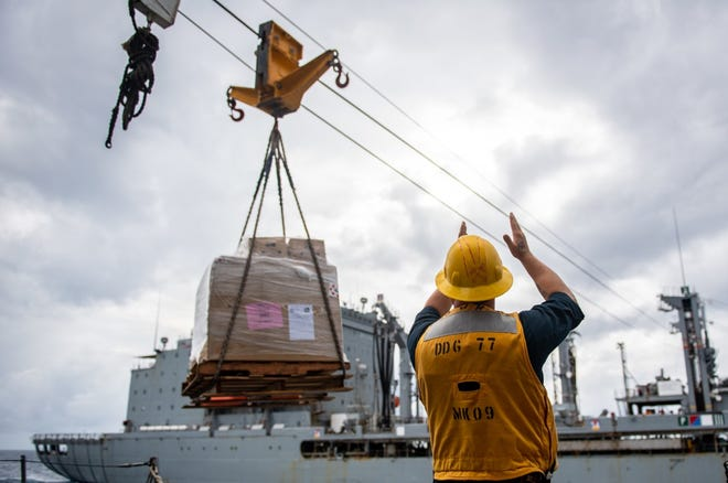 Boatswain's Mate 1st Class Samuel Lippincott, from Aliquippa, guides a cargo transfer aboard Arleigh Burke-class guided-missile destroyer USS O'Kane (DDG 77) during a replenishment-at-sea with Henry J. Kaiser-class underway replenishment oiler USNS Tippecanoe (T-AO 199) in August in the South China Sea. O'Kane is deployed supporting Commander, Task Force (CTF) 71/Destroyer Squadron (DESRON) 15, the Navy's largest forward-deployed DESRON and U.S. 7th Fleet's principal surface force.