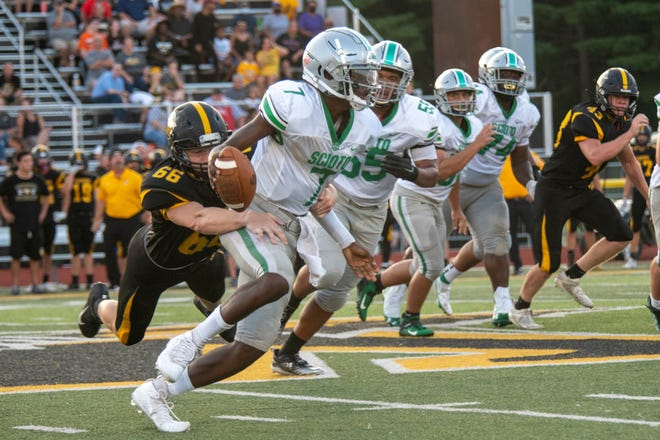 Watkins Memorial's Derek Knoblauch attempts to bring down Dublin Scioto quarterback Amare Jenkins on Aug. 27. The visiting Irish rallied from a 27-7 deficit to beat the Warriors 35-27.