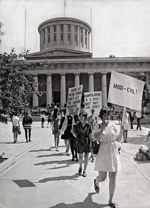 In 1970, attendees at a Women's Liberation meeting picket to protest midi-length fashions. They were on their way to the Lazarus department store. A peace group, which identified itself as Quakers, took advantage of the situation and members read a list of Vietnam War dead.