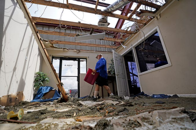 Rene Hebert cleans out the family's destroyed offices in the aftermath of Hurricane Ida Monday in Houma, Louisiana.