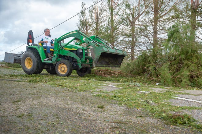 Robert Lirette clears debris Aug. 30 from the road and neighbors' yards after Hurricane Ida passed through Houma.