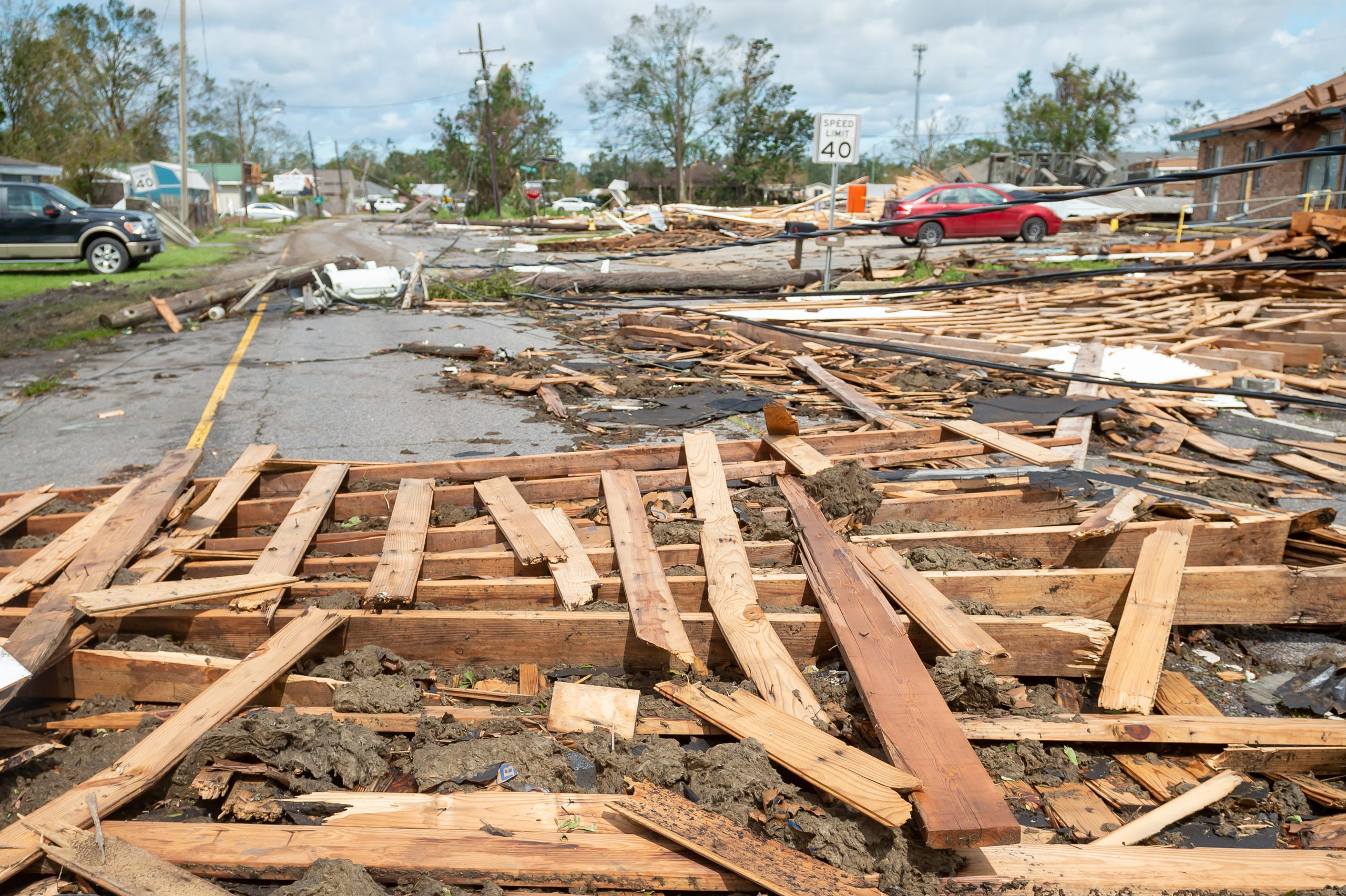 Parts of a building and other storm debris block a Houma road on Monday.