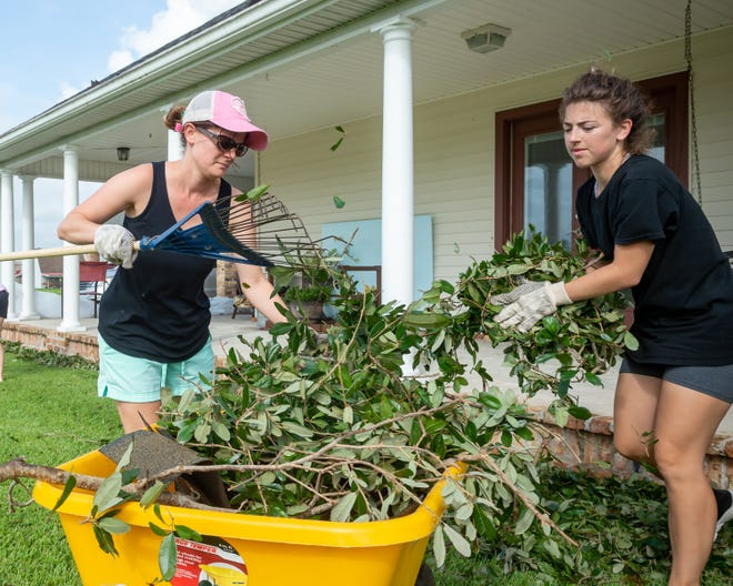 Kayla Voison and Mariah Foret clean up debris from Hurricane Ida in Houma, LA. Monday, Aug. 30, 2021.