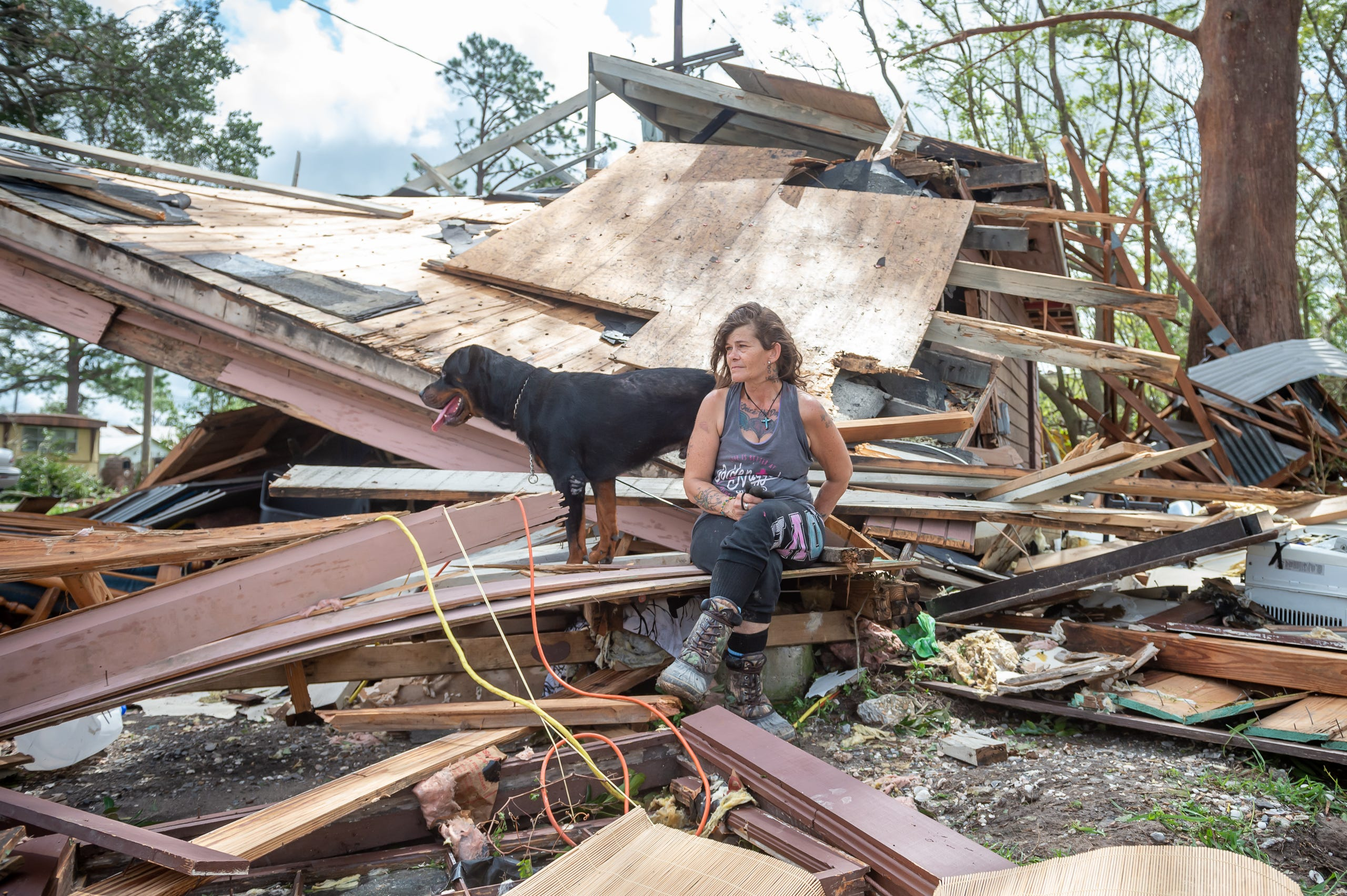 Fran Tribe and her dog Dave sit outside home destroyed by Hurricane Ida in Houma, LA. Monday, Aug. 30, 2021.