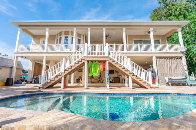The upper deck of this one-of-a-kind canal-front property in Astor overlooks the waterfront oasis, with an in-ground heated swimming pool, tiki hut and fire pit.