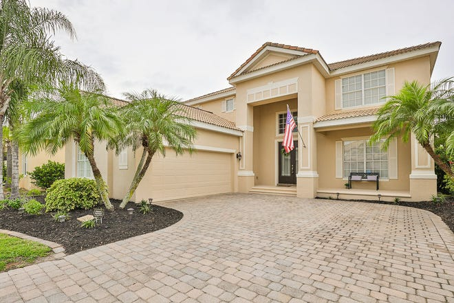 A paver driveway leads to this luxurious two-story home that sits on a fenced-in lush lakefront lot in Venetian Bay.