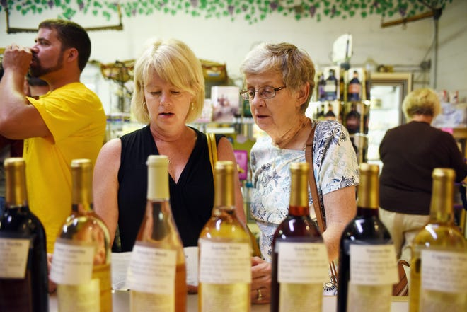 Kallie Rich and Carol Rager of Candid, Missouri, look through wines Aug. 31, 2014, as Illinois' oldest winery opens its doors during the 77th Annual Grape Festival to big crowds near Nauvoo.