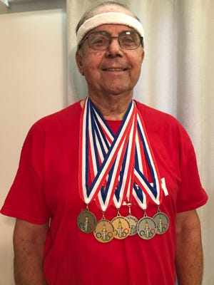 Eighty-three-year-old Mike Cherry of Geneseo shows the six medals he won at the QC Senior Olympics held July 31 at Augustana's Paul V. Olsen Track in Rock Island.