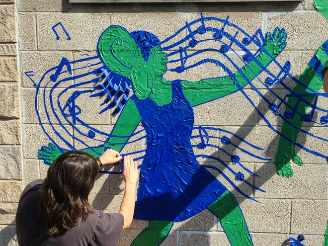 Professional Tape Art artist Leah Smith adds some finer detail to the group's work on a mural evoking the Lotus World Music & Arts Festival Saturday in downtown Bloomington.