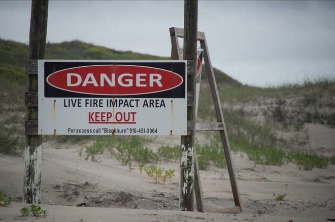 Danger signs stand along the border of Browns Island to warn beach goers not to walk into the impact area. Camp Lejeune's Browns Island Policy is intended to protect boaters and beach goers from the frequent live-fire training exercises conducted in the area and the danger of unexploded ordnance.