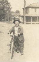 Elmer Beverly is shown here in Milan with a bicycle that was made specially for him. Beverly worked for the railroad.