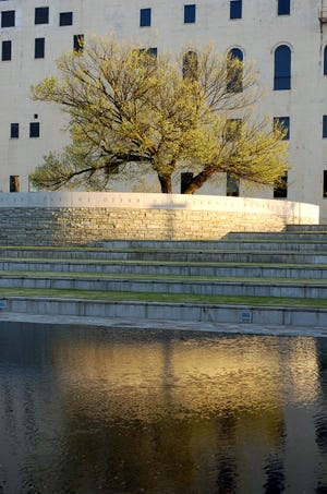 The Oklahoma City National Memorial & Museum's Survivor Tree and Reflecting Pool are shown at sunrise.