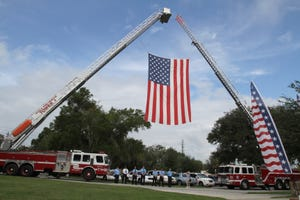 Ladder trucks with both Ocala Fire Rescue and Marion County Fire Rescue support a large American flag during the 9/11 Remembrance ceremony at the Ocala-Marion County Veterans Memorial Park in Ocala on Saturday, Sept. 10, 2011.