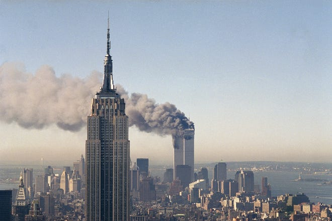 This Sept. 11, 2001 file photo shows the twin towers of the World Trade Center burn behind the Empire State Building in New York City after terrorists crashed two planes into the towers, causing both to collapse.