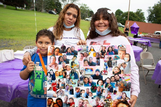 The children of Michael Anthony Martins held up a collage of their father's photos at a vigil held in Stroudsburg on Sunday, Aug. 29, 2021. Martins was prescribed pain medication following an injury and became addicted. He died of an overdose.