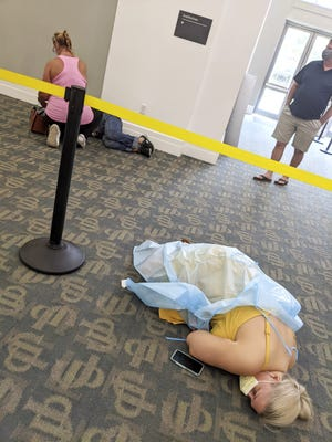 In this photo provided by Louie Lopez, sick people lie on the floor in a medical facility in Jacksonville, Fla., on Wednesday, Aug. 18, 2021. Lopez took the photo while waiting more than 2.5 hours to get antibody treatment at a facility run by the state. While he waited, he watched the room fill up with extremely sick patients. (Louie Lopez via AP)