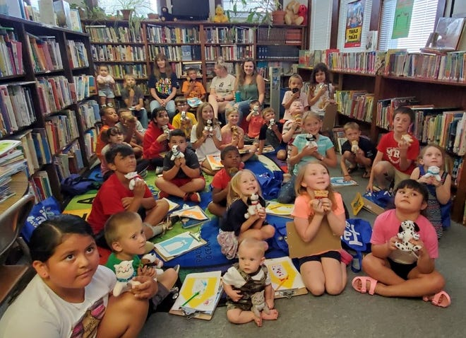 Macksville kids show off their new stuffed kittens and puppies at a Summer Reading Story Time.