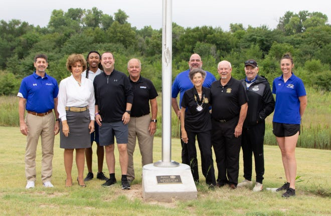 Pratt Rotary Club members, joined by Pratt Community College leadership and student representatives, stand with a flag pole made possible by rotary funds and placed at the new PCC Track and Field Complex in Pratt.
