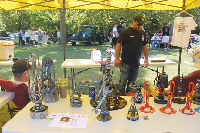 Taylor Schmidt, City of Pratt Fire Department, keeps an eye on special car show prizes while selling raffle tickets Saturday for t-shirts and other miscellaneous items.