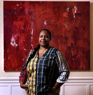 """Gem Barros with her painting  """"Red Rain"""" in the Nonviolence Institute in Providence. Barros lost her daughter to violence in the city and found solace and forward motion in painting."""