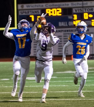 Southeast of Saline receiver Michael Murray (9) hauls in a long pass between a pair of Collegiate defenders during last year's Class 3A playoff game in Wichita.