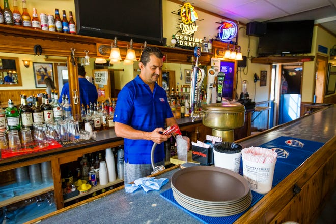 Owner Tony Simeri pours a water Monday at Simeri's Old Town Tap in South Bend.