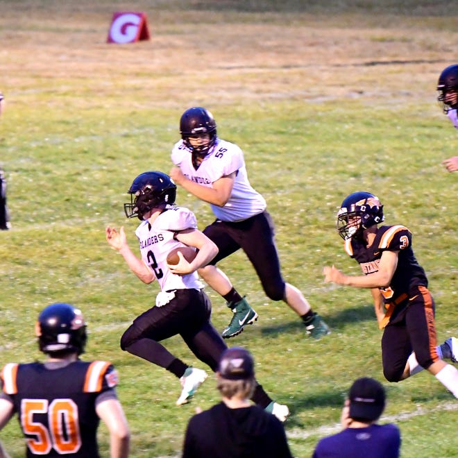 Cedarville-DeTour quarterback Cason Smith finds some running room and looks for a block from Ty Norris (55) during a football opener at Munising Friday night.