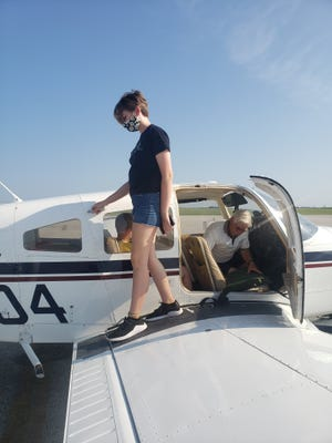 Cosette Komnick disembarks from a low-wing Piper at the Kewanee Municipal Airport Saturday. The pilot, George Bedeian, was one of five volunteer pilots to give free airplane rides to members of the Kewanee Girl Scouts Troop 4444. The airplane rides are part of the EAA Young Eagles program. Komnick's younger brother, Edmond, went along for the ride.