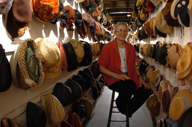 Peggy Farrell of Farrell's Costumes, Ltd. sits amid some of the thousands of hats in her collection in Wilmington, NC, Wednesday, May 31, 2006.