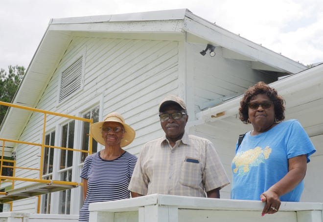Queenie Green, Vernon Cooper and Teresa Badger, members of the Holt's Chapel Community Center, stand outside of the former African American elementary school, which dates back to 1921.