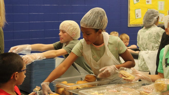 Fourth- and fifth-grade students am O.M. Tiffany Elementary School help serve lunch to other students.