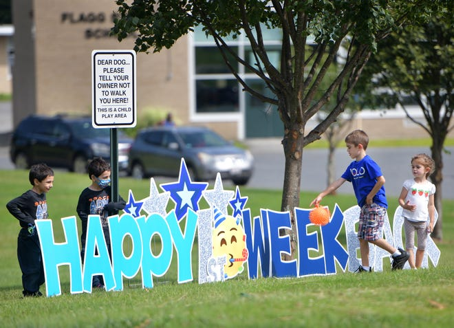 Kids check out the giant sign welcoming them back to Flagg Street School on Monday in Worcester, as their parents photograph them.