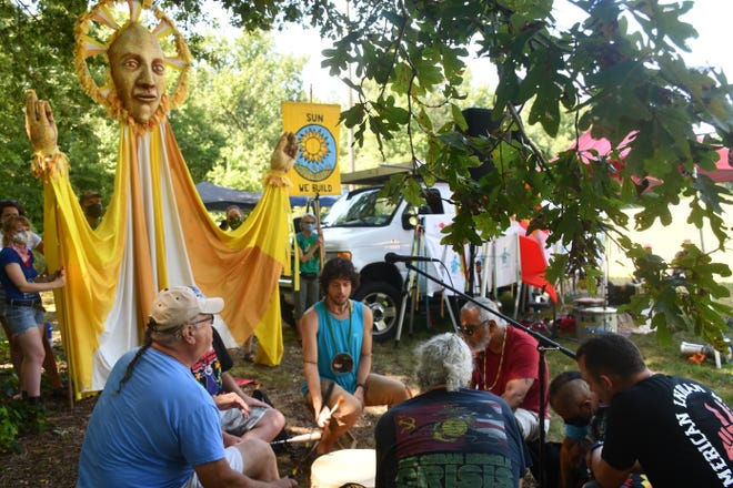 Members of the Gray Wolf Juniors perform a drum circle before an art piece meant to symbolize the Sun at a gathering Saturday, Aug. 28, 2021.