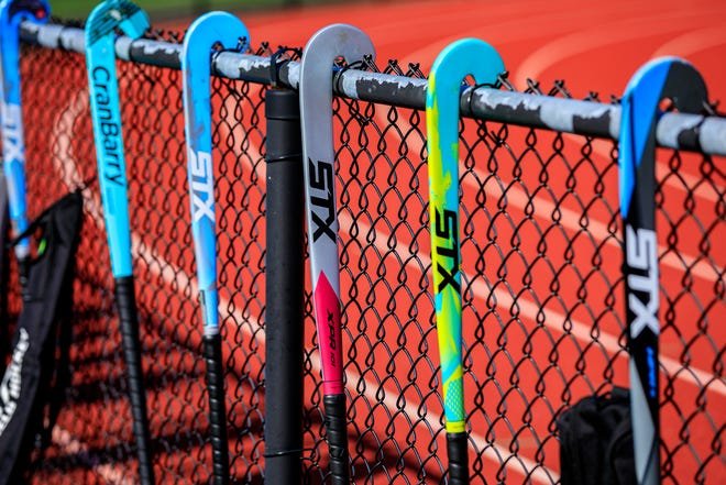 Field hockey sticks are lined up on the fence enclosing the field.