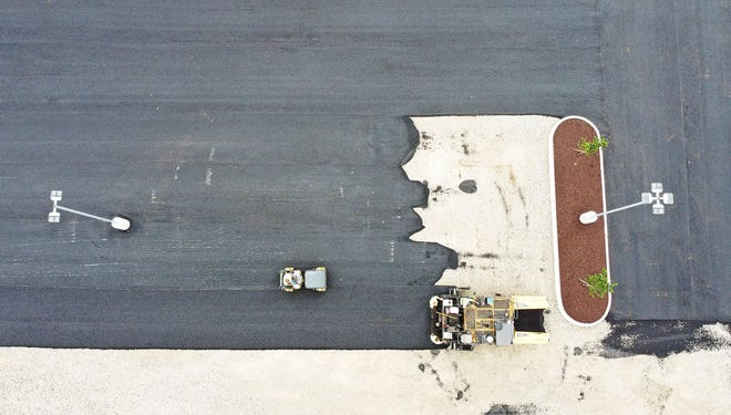 Workers can be seen in this drone's-eye view applying asphalt to the parking lot of the new Aldi grocery store at 1885 E. Mansfield St. The store is scheduled to open on Sept. 9. The new store is being built on the site of the former Al Smith's Place, which was demolished in January to make way for Aldi.